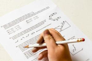 鉛筆をもってテスト用紙に書き込んでいる写真